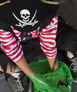 child dressed as pirate digging through green plastic bag filled with candy