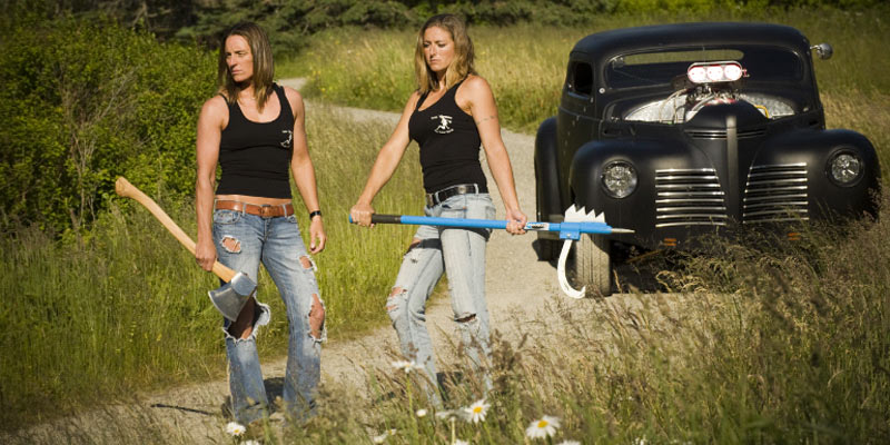 two women stand looking tough with axes, there's a black classic car in the background