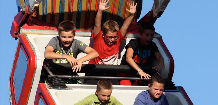 kids on a fair ride that goes up and down, one has his arms up
