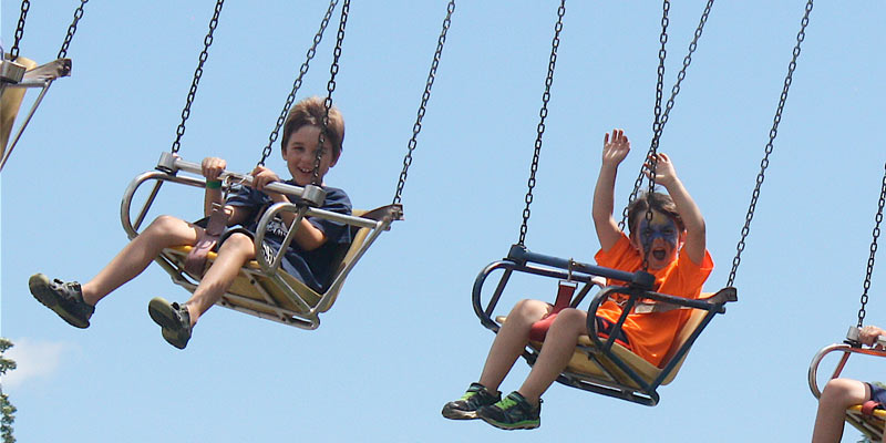 two little boys having a great time on the vertigo swing rides at the fair