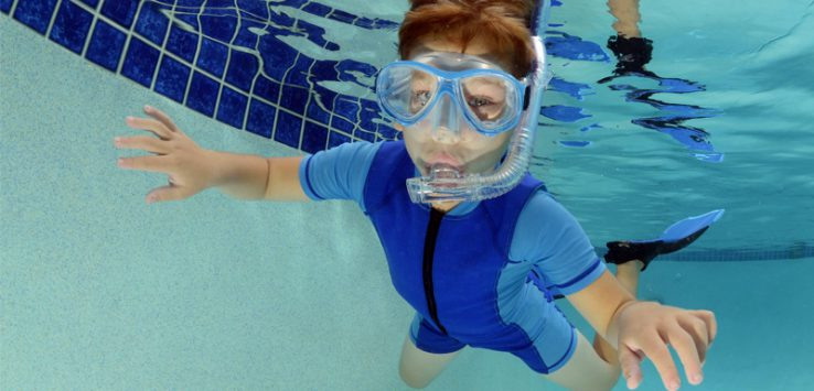 a kid with goggles swimming underwater in a pool