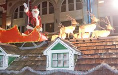 Santa with his reindeer on a float on top of a fake house