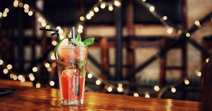 a pink cocktail with herbs on a bar with Christmas lights in the background