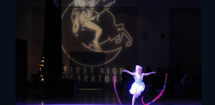a little girl ballerina dancing on a stage with a First Night logo behind her