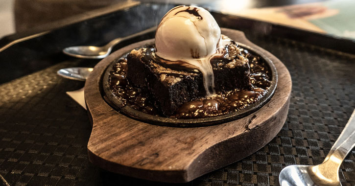 a chocolate brownie in a restaurant with a scoop of vanilla ice cream on top