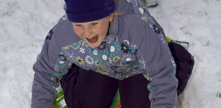 young girl on snow tube