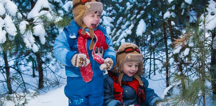 two little boys playing in the snow, one is laughing