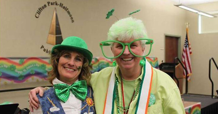 two women in a library dressed up for St. Patrick's Day