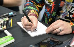 the arm of a comic book person signing something
