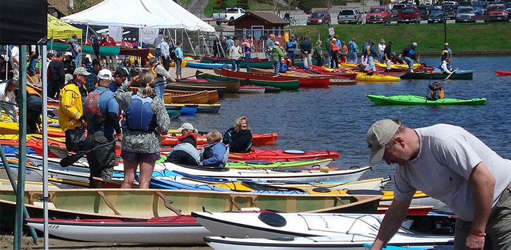 a lot of paddleboats by the water, crowd of people