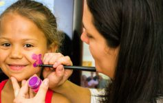 a little girl getting her face painted
