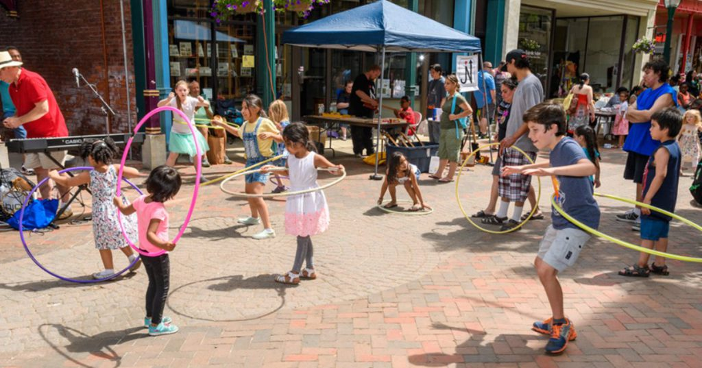 kids hula hooping on sidewalk area