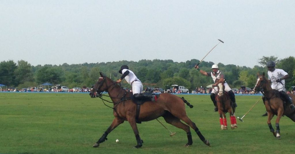 three polo players on horses