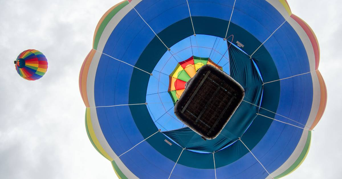 looking up at the bottom of hot air balloons taking to the sky