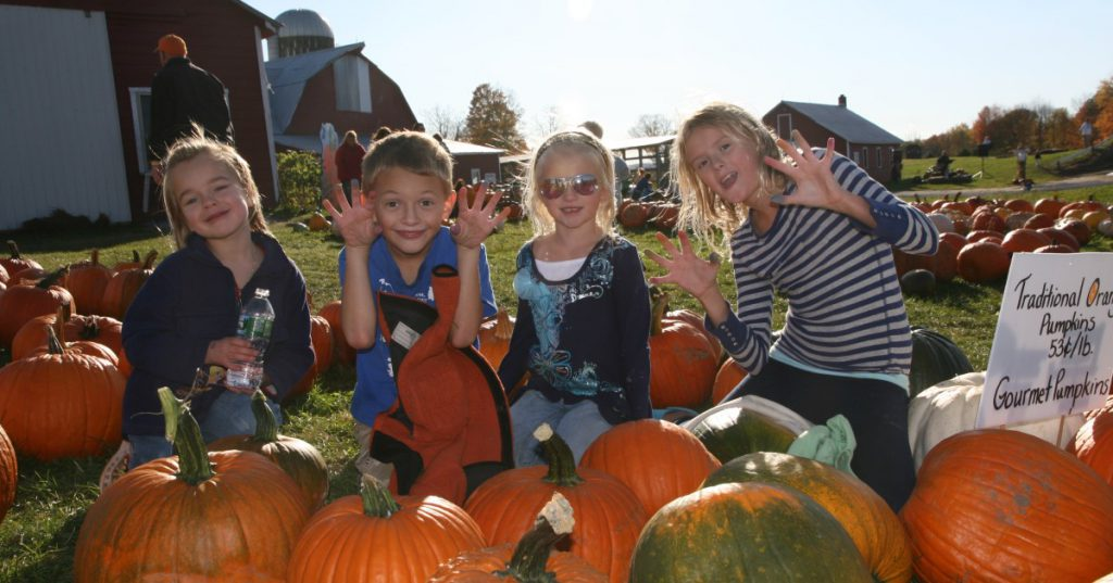 four kids with pumpkins