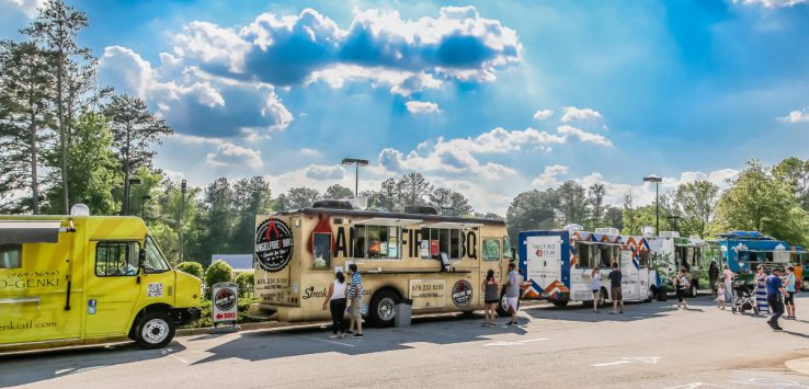lineup of food trucks with people nearby