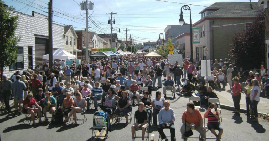 people in chairs at a street festival