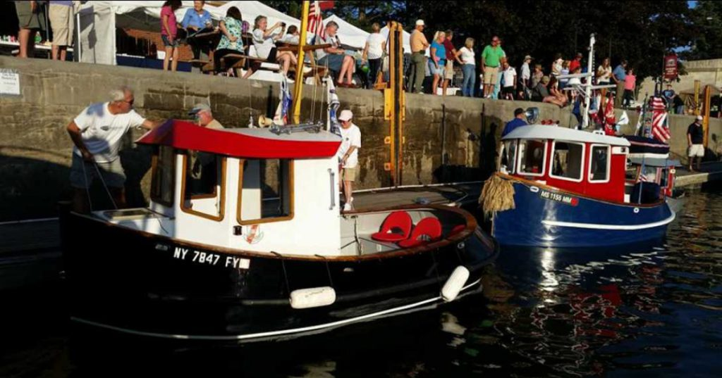 two tugboats by cement wall with people nearby