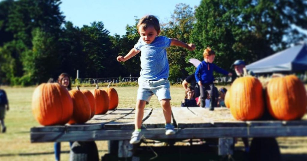 kid jumping near pumpkin