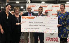 dunkin' and toys for tots representatives holding a large check