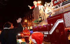person waving at santa in fire truck