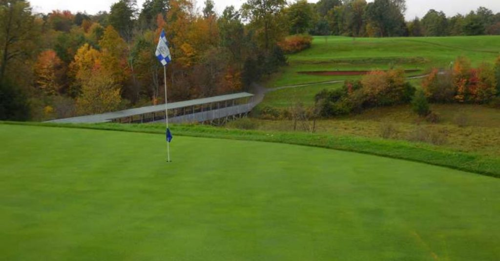 golf course flagpole with view of trees with fall colors