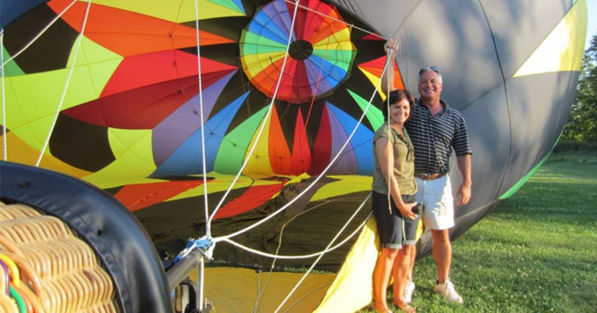 two people standing next to a hot air balloon