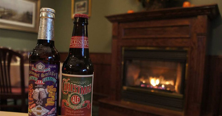 two beers on a table in front of a roaring fireplace