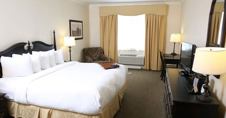 a hotel room with a bed with white sheets, a desk, lamps, and a window with light brown curtains