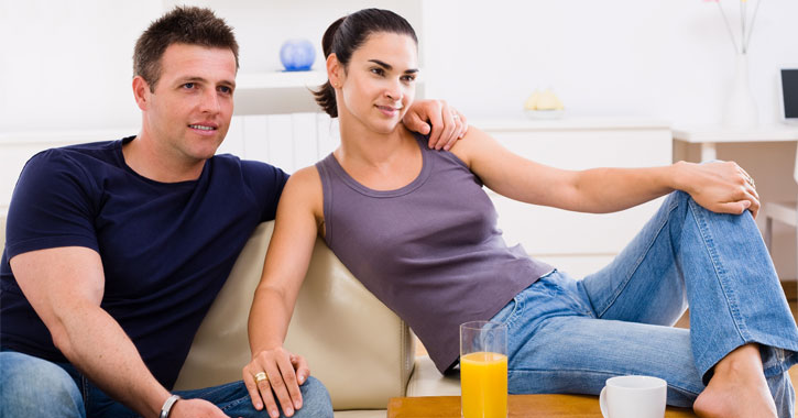 a young attractive couple on a couch watching TV
