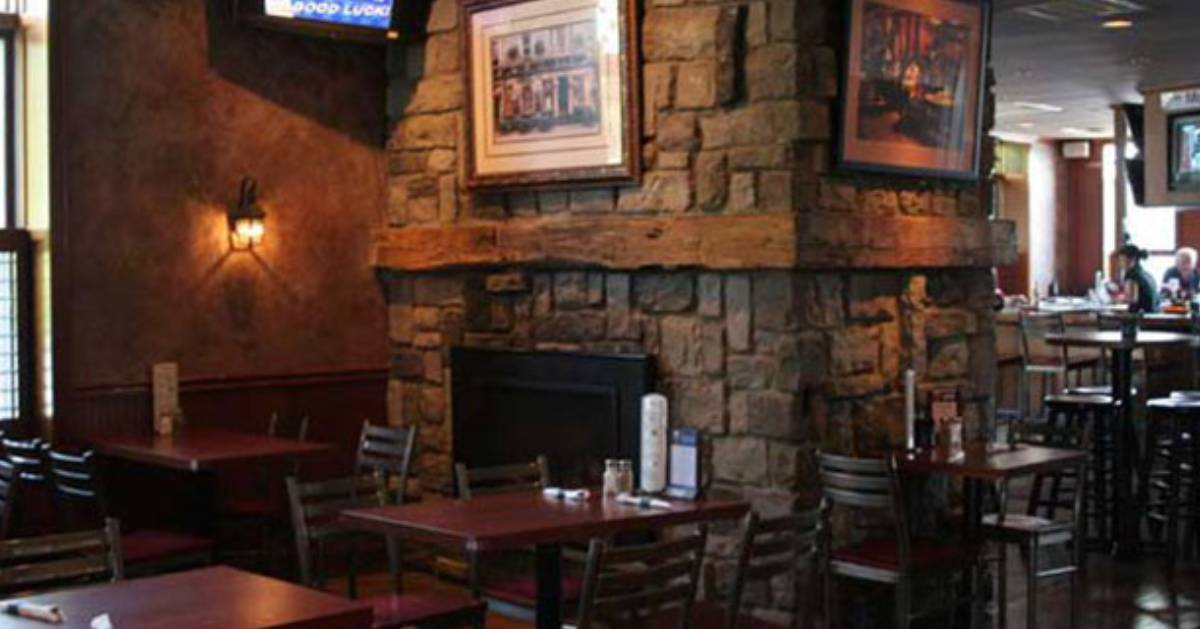a stone fireplace near tables in a dining area