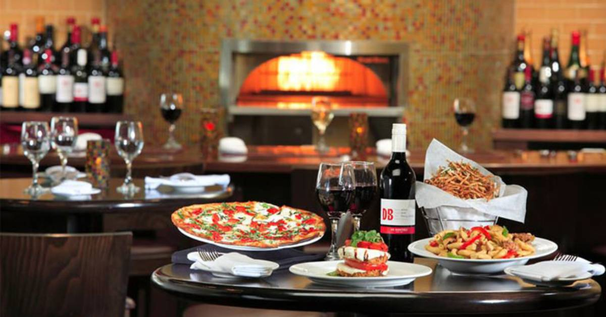pizza and wine on tables and a pizza oven in the back of the room