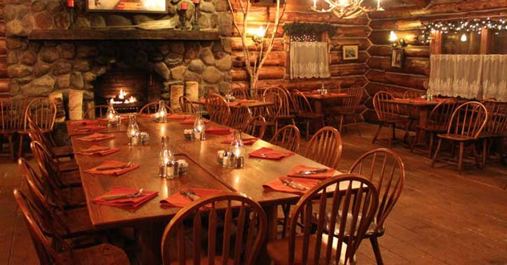 tables and chairs set up in an Adirondack-style restaurant with a fire in the fireplace