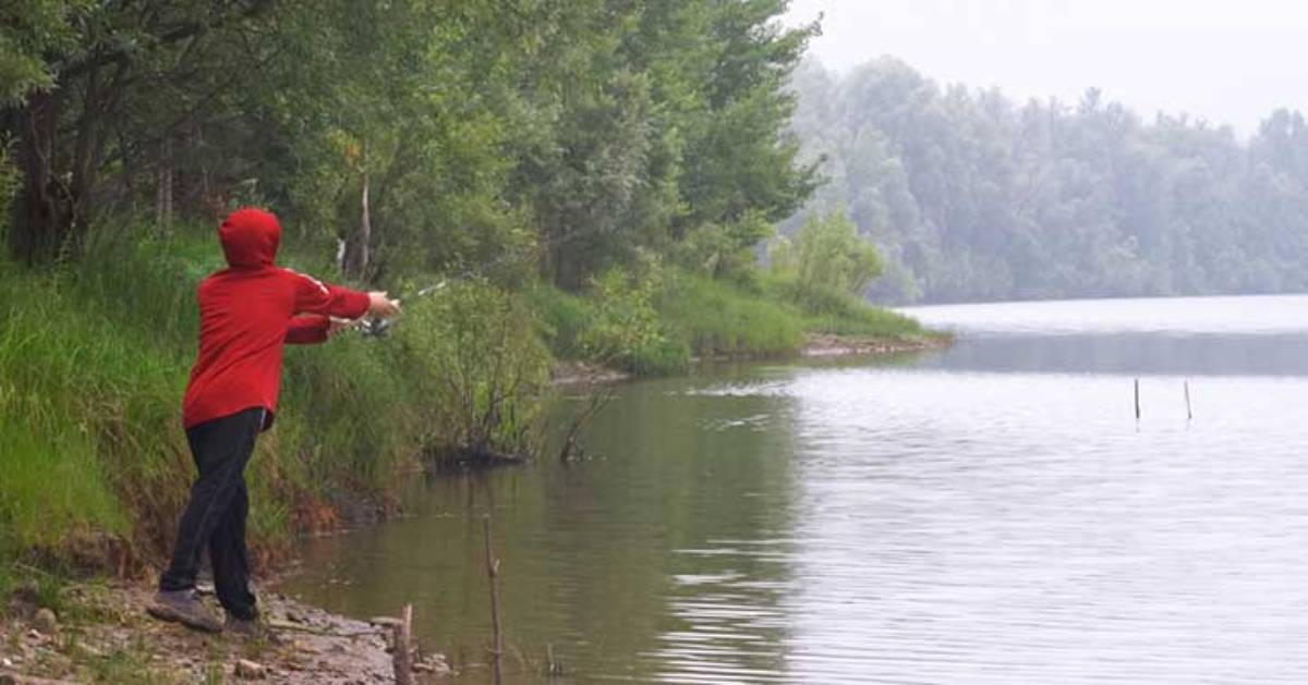 person with red sweater casting fishing line from shore
