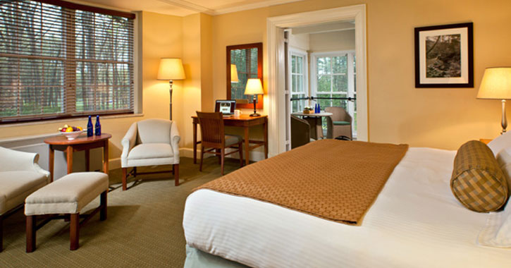 a hotel room with a bed with white and brown design, chairs, and an adjoining room