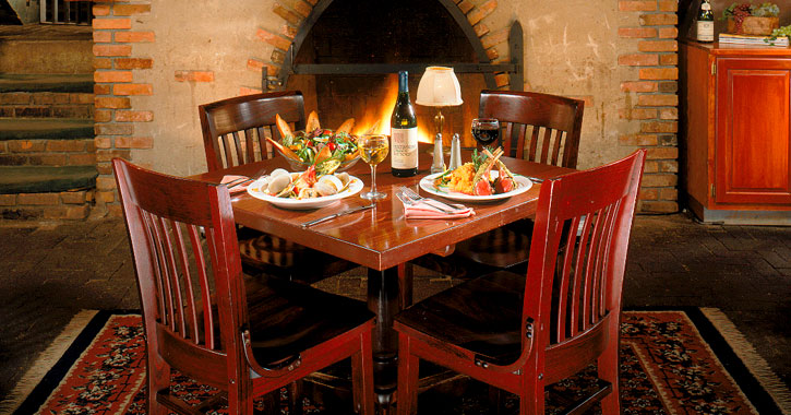a table set up in a restaurant in front of a fireplace