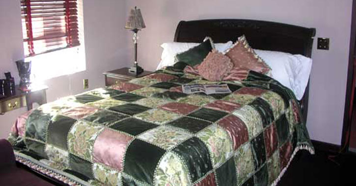 a green and pink checkered bedspread on a bed