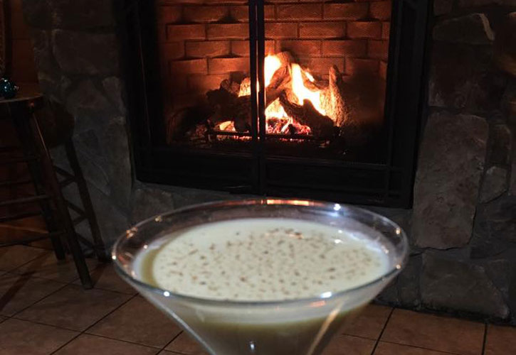 an eggnog martini in front of a roaring fire