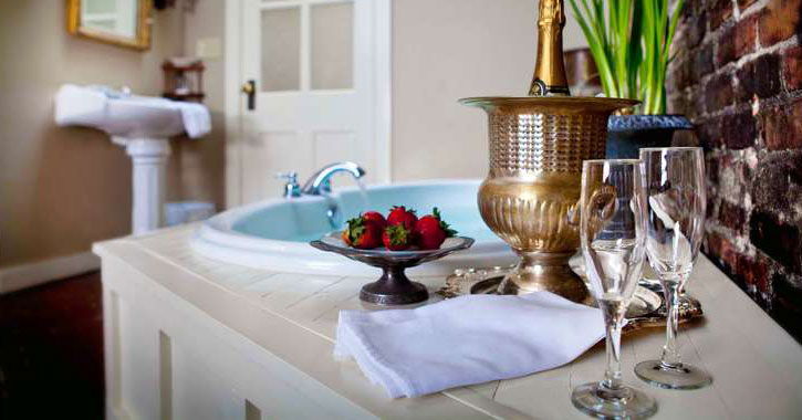 champagne, glasses, and strawberries set up beside a hotel bathtub