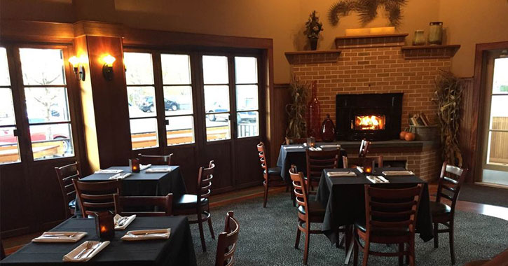 tables set up in a restaurant with a fire in the fireplace