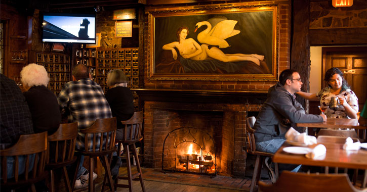 people seated in a restaurant by a fire, th ere's a large painting of a naked woman and a swan above the fire