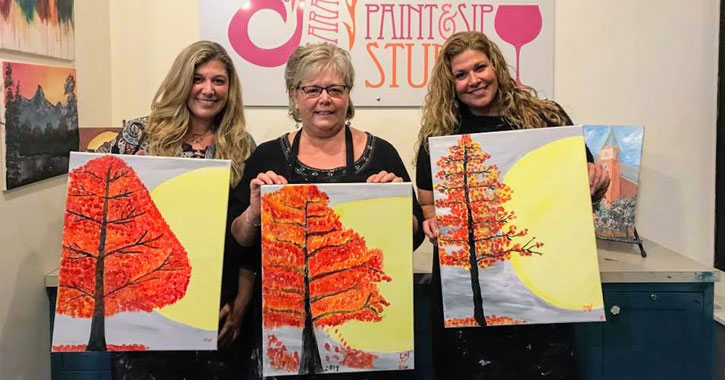 three women holding up paintings of a tree