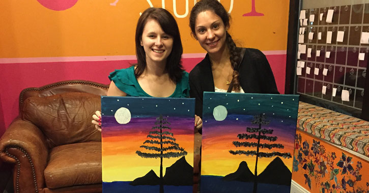 two young women holding up their paintings of a tree at a paint and sip studio