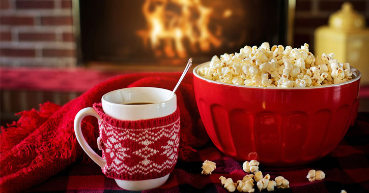 a cup of coffee and a bowl of popcorn in front of a roaring fire