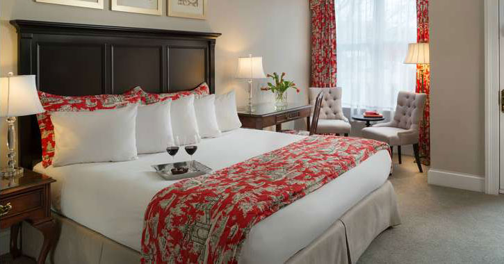 a bed in a hotel room with a white and red pattern, tray of two wine glasses with red wine on bed