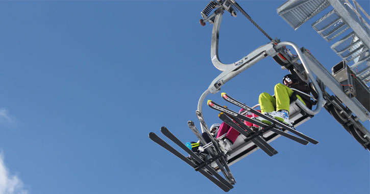 a view looking up at a ski lift, just seeing people's legs and skis and the sky