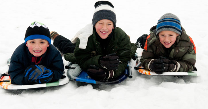 three boys in a row on their stomachs on sleds smiling