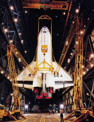 Space Shuttle being hoisted into the air by cranes