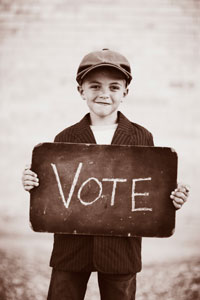 Young boy in newsboy hat and suit jacket holding sign that reads 'vote'