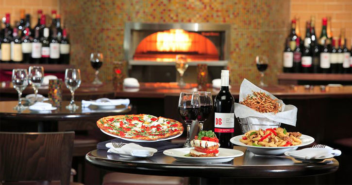 a spread of pizza, pasta, and more with a fire and wine bottles in the background